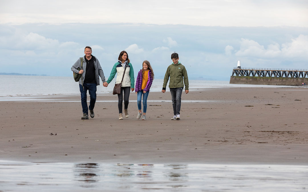 Family walking along the Cumbrian coast at Maryport
